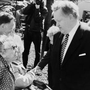 Martti Ahtisaari skakar hand med en kvinna på ett torg, omgiven av andra människor