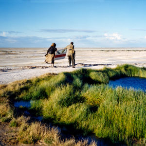 Kaksi ihmistä kävelee autiomaassa, selin, kaukaa. Kuva elokuvasta Maailman ääriin.