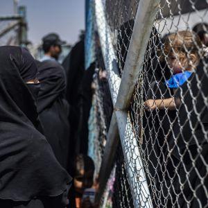 Kvinnor och barn väntar på att få stiga ombord på en buss som tar dem ut från lägret al-Hol i nordöstra Syrien 3.6.2019