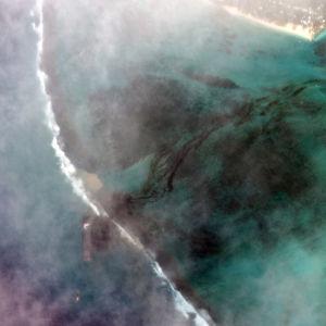 En sattelitbild tagen på ett fartyg. Till höger ser man svart olja som läckt ut från fartyget. Vattnet runt omkring är turkost, men färgas av oljan.