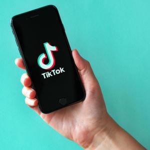 En person håller i en telefon där en logo syns. Det står tiktok. I bakgrunden syns en mintgrön vägg.