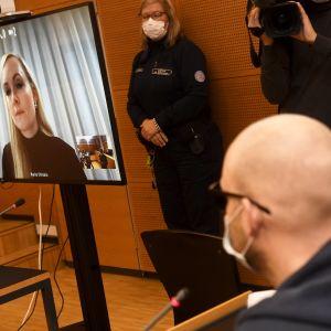Inrikesminister Maria Ohisalo syns på en skärm i en rättegångssal.