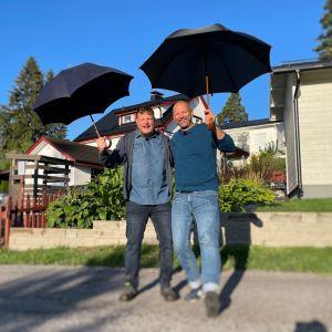 Två personer står i solskenet med paraplyn.