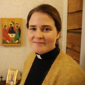 Mari Leppänen, en dam med mörkt hår bakåtkammat i hästsvans, gul tröja och en svart dräkt med prästkrage.