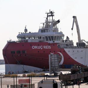 Punavalkoinen alus on satamalaiturissa. Edustalla näkyy kuorma-auto. Laivan kyljessä lukee Oruç Reis ja siinä on kuvattuna myös Turkin lipun tähti ja puolikuu.