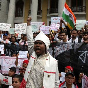 Bild från demonstration i Bangalore i Indien mot. På bilden syns en vitklädd man i förgrunden som räcker upp sin knutna näve ovanför hvuudet.