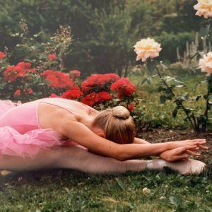 Mari Rosendahl balettipuku ja -tossut yllään nurmikolla sirossa istunnassa ylävartalo suorien jalkojen yli taivutettuna. Taustalla ruusuistutuksia.