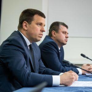 Estlands premiärminister Jüri Ratas och utrikesminister Urmas Reinsalu sitter vid ett bord med mikrofoner framför sig.