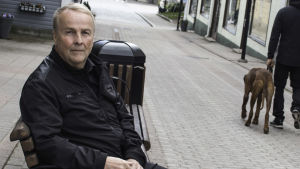 En blond man med svarta kläder sitter på en bänk som finns på Kungsgatan i Ekenäs. Han ser allvarlig ut.