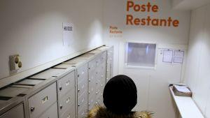 Asunnoton ihminen hakeaa postiaan poste restante -noutopisteestä Helsingissä.