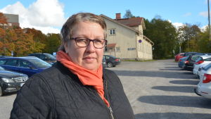 En kvinna poserar på en parkeringsplats.