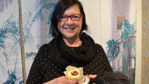 birgitta palmqvist håller i en runebergstårta som ser ut som ett muffins