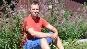 en man i röd t-skjorta och blå shorts sitter på en låg betongmur. Han omgärdas av duntrav, det vill säga rödlila blommor.