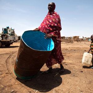 Kvinna bär en vattentank i ett flyktingläger i Sydsudan.