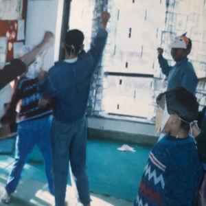 Nepalilaisia pikkupoikia tanssimassa luokkahuoneessa paperinaamiot kasvoillaan.