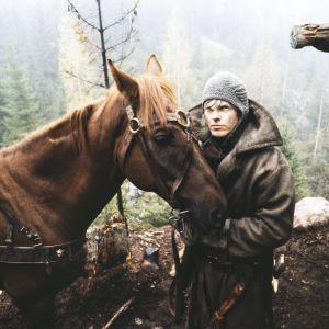 Näyttelijä Tom Wentzel Lemmingin roolissa tv-sarjassa Rauta-aika. Lemminki pitelee hevosta.