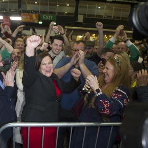 En massa människor som jublar och viftar med händerna.