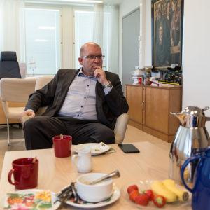Industrifackets ordförande Riku Aalto sitter framför ett lågt bord med frukost på. I förgrunden syns en kaffekanna och en mjölkkanna.
