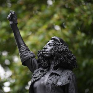 Mustaa naista esittävä patsas. Naisen käsi on nyrkissä.