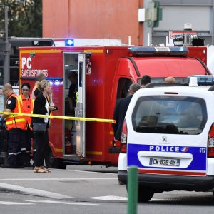 Polisbilar och ambulanser på en gata.