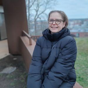Markita Tiheäsalo, en dam med glasögon och mörkblå dunjacka, sitter vid en mur en dimmig novemberdag.