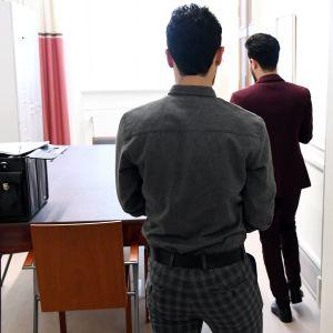 Två svarthåriga män med ryggen till.