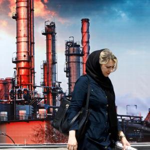 En kvinna framför ett oljeraffinaderi i Iran.