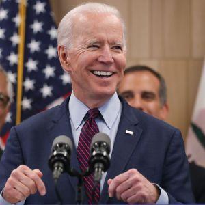 Joe Biden ler mot kameran.