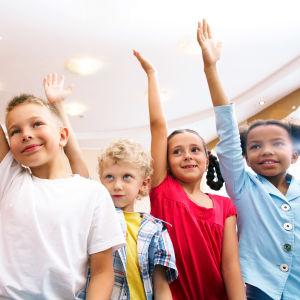 Kuvassa on alakoululaisia lapsia viittaamassa.