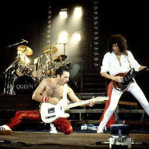 Queen live i Belgien 1982. Freddie Mercury på knä spelar gitarr bredvid Brian May.