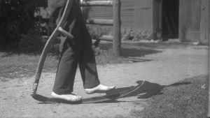 En man går barfota på en lie. Bilden är tagen 1931 i Ingå, Lill-Breds.