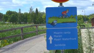 En trafikskylt står framför en bro i trä. Skylten visar en bild på en cyklist och en fisk som kommer upp ur vattnet och visar tungan åt cyklisten. Under bilden står det Maren, ovanom finns ett märke som säger att man inte får köra bil eller motorcykel.