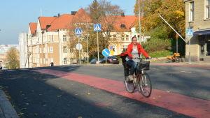 En kvinna cyklar på en röd cykelbana.