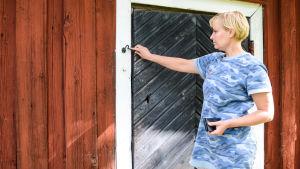 En kvinna i blå tunika står vid en röd boda. Hon håller på med att antingen öppna eller stänga dörren.