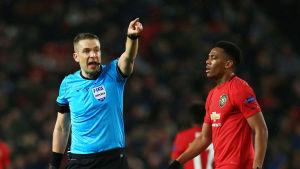 Mattias Gestranius ropar och pekar medan Anthony Martial går med bollen.