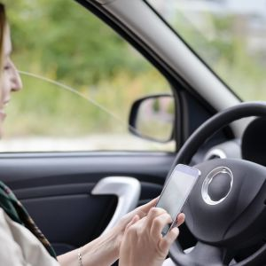 En businesskvinna sitter i en bil och skriver ett sms.