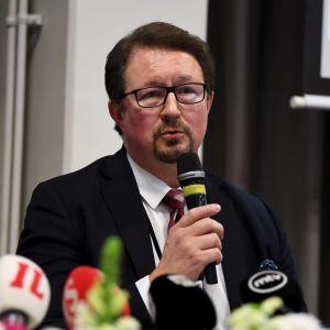 En man talar i en mikrofon på en presskonferens.
