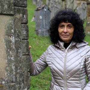 Rajaa Nadler står vid en gravsten på den judiska begravningsplatsen i Ermreuth