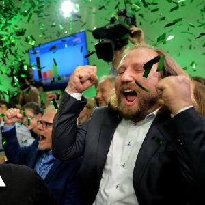 Glada människor firar på det tyska gröna partiets valvaka i Bayern. Över dem regnar det grönt konfetti