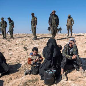 Soldater övervakar kvinnor och barn som flytt från IS-fästet i Baghouz, Syrien 12.2.2019