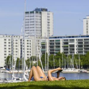 Nainen ottaa aurinkoa nurmikolla Helsingin Tervasaaressa.
