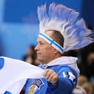 Finländsk hockeyfan viftar med Finlands flagga iklädd hockeyskjorta och med blåvit peruk på huvudet.