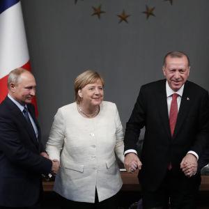 Rysslands president Vladimir Putin, Tysklands förbundskansler Angela Merkel, Turkiets president Recep Tayyip Erdoğan och Frankrikes president Emmanuel Macron håller varandras händer efter avslutat Syrienmöte i Istanbul.