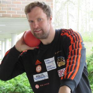 En man med lite lockigt mörkt hår och skägg med en röd kula mot halsen. Han är kulstötare och poserar framför kameran.
