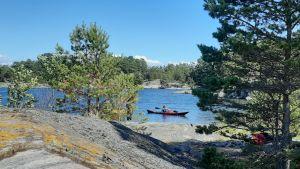 En röd kajak kommer till en klippig strand.