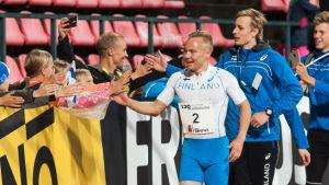 Tre friidrottare med Joonas Rinne i spetsen tackar publiken.