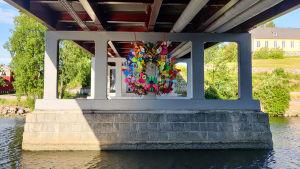 En stor krans av färggranna plastföremål hänger under en bro.