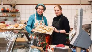 Två kvinnor står bakom en butiksdisk och håller i en plåt med jultårtor.