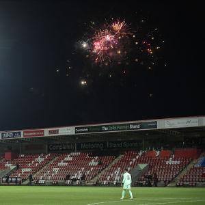 Fyrverkerier syns vid arenan när Cheltenham Town spelar mot Manchester City.