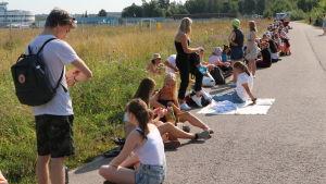 Ungdomar köar till Ed Sheeran-konsert sittande på marken utomhus.
